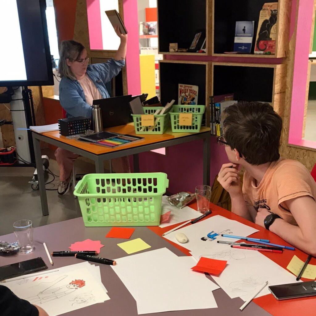 Labcoach Jasha zit achter ene tafel en geeft een workshop Manga tekenen, voor haar is een deelnemer te zien.